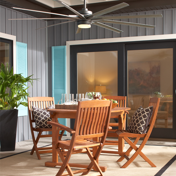 Pictured on an outdoor patio, above a dining table is a large 9-blade outdoor ceiling fan .